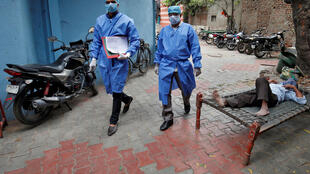 Police officers in protective suits arrive in a residential area to check on people under home quarantine in Ahmedabad, India, on March 25, 2020, during a 21-day nationwide lockdown to limit the spread of the coronavirus.