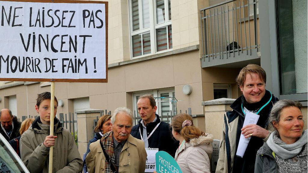 """Un miembro del comité de apoyo del tetrapléjico francés Vincent Lambert sostiene un cartel que dice """"No dejes que Vincent muera de hambre"""" mientras protesta frente al hospital de Sebastopol en Reims, al este de Francia, el 19 de mayo de 2019."""