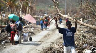 Des Haïtiens marchent à Les Cayes, ville dévastée par l'ouragan, le 10 octobre 2016.