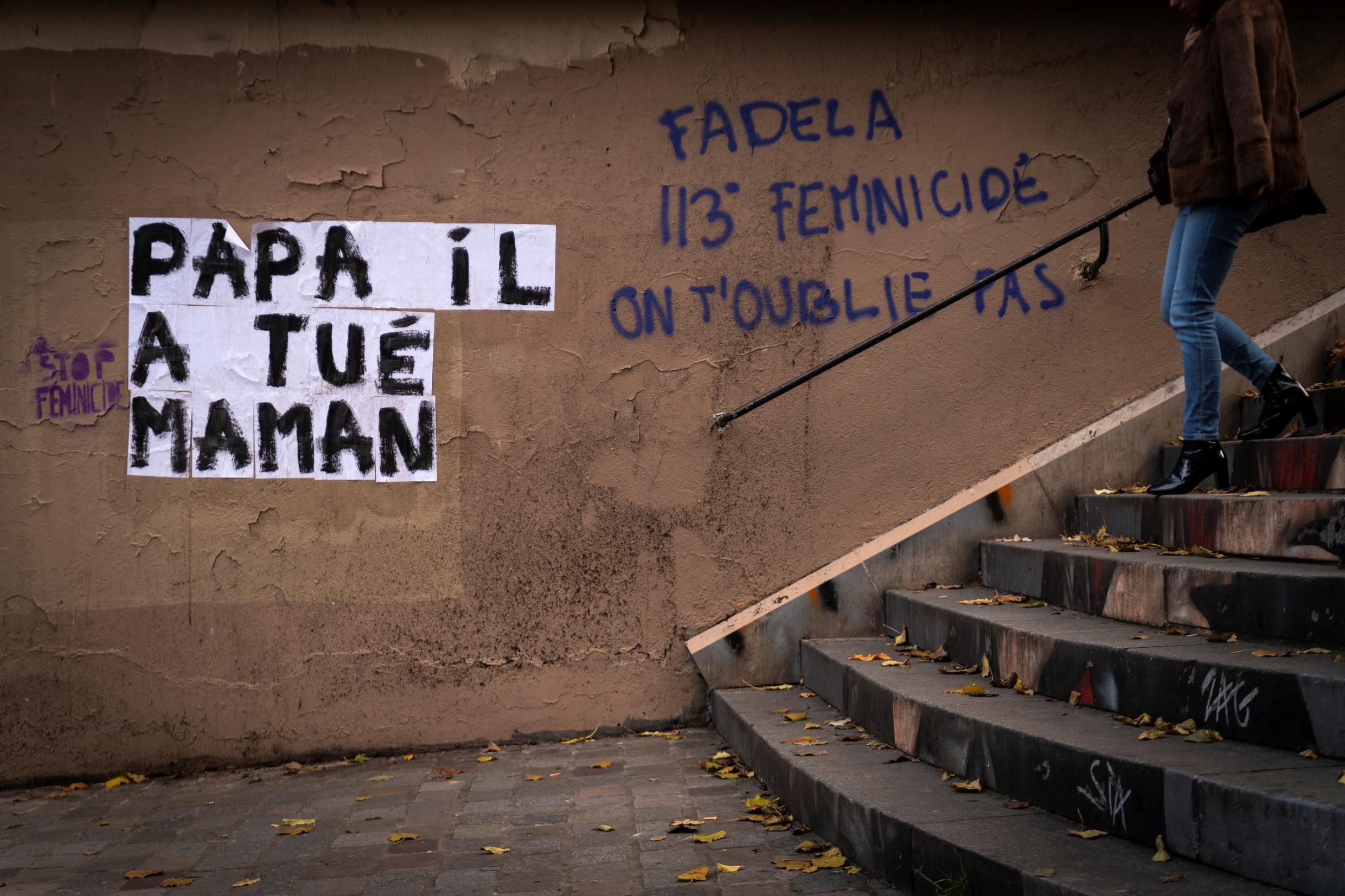 A woman walks by a banner reading 'daddy, he killed mummy' as part of a campaign against domestic abuse in France, November 25 2019.
