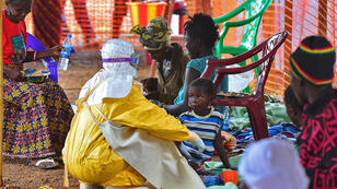 A medical worker feeds a child victim of Ebola at a facility in Kailahun, Sierra Leone, on August 15, 2014.