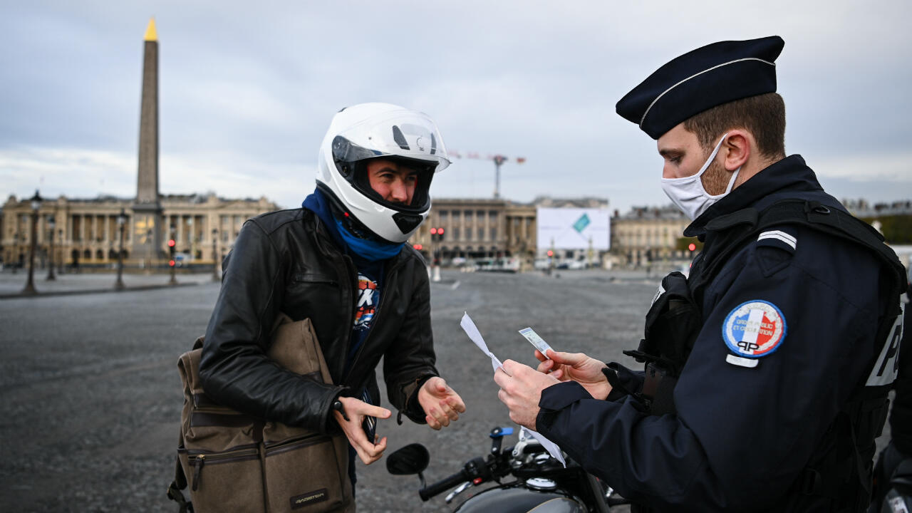 French police officers check a driving authorization form in Place de la Concorde in central Paris on November 13, 2020, during the second Covid-19 lockdown in France.