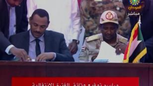 El representante de las formaciones civiles, Ahmad al-Rabie (izq.) y el vicepresidente del Consejo Militar Transitorio, el general Mohamed Hamdan Dagalo, durante la firma del acuerdo en Jartum, Sudán. 17 de agosto de 2019.