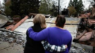 Irma Corona, a la derecha, consuela a una vecina frente a los restos de su casa, después de que las dos regresaran por primera vez desde el Camp Fire en Paradise, California, EE. UU., el 22 de noviembre de 2018.