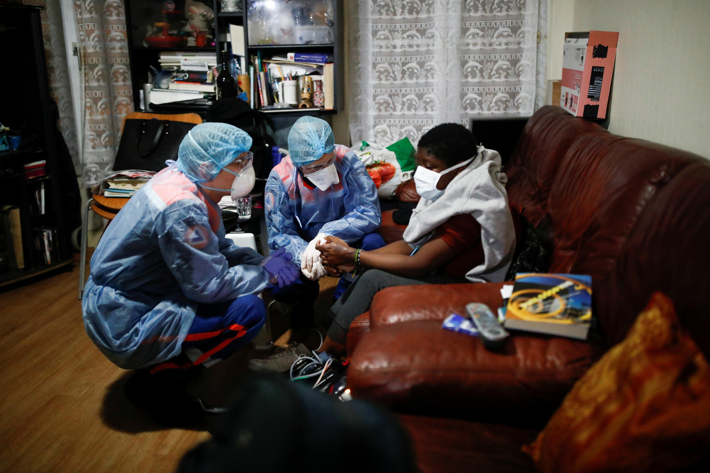 Members of the French civil protection service talk with an 18-year-old woman suspected of being infected with the coronavirus  in Paris, France, on April 4, 2020.