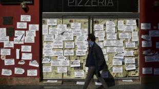 Un hombre camina frente a una pizzería cerrada que permanece cubierta con papeles de reclamos de los antiguos empleados, en Buenos Aires, el 17 de junio de 2020, en medio de la pandemia de coronavirus