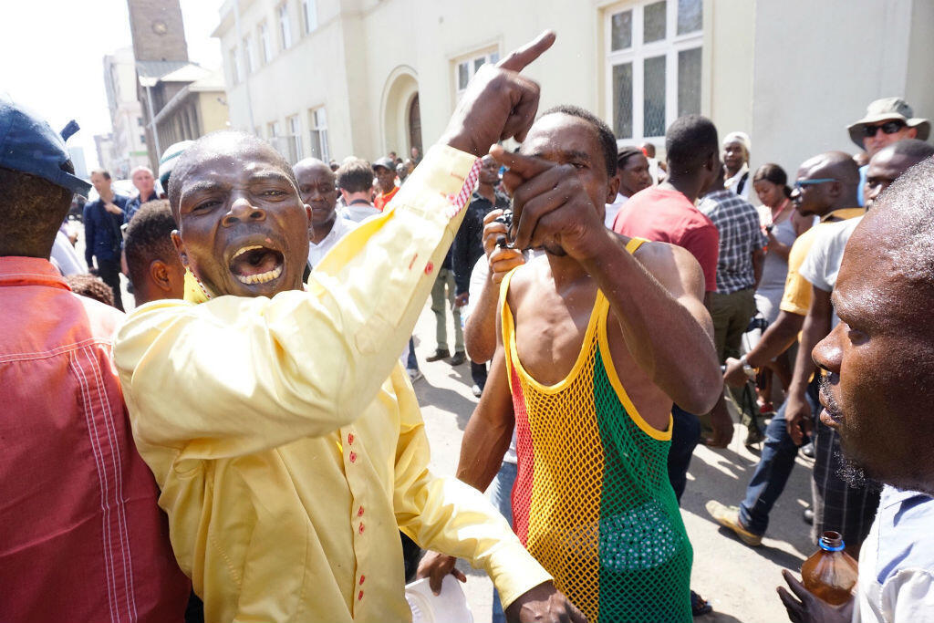 """Des centaines de personnes étaient massées à l'extérieur du Parlement, aux cris de """"Mugabe doit partir"""", à Harare mardi 21 novembre."""
