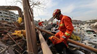 Un trabajador realiza tareas con un perro de rescate en el lugar de la explosión en Ningbo, provincia de Zhejiang, China, el 26 de noviembre de 2017.
