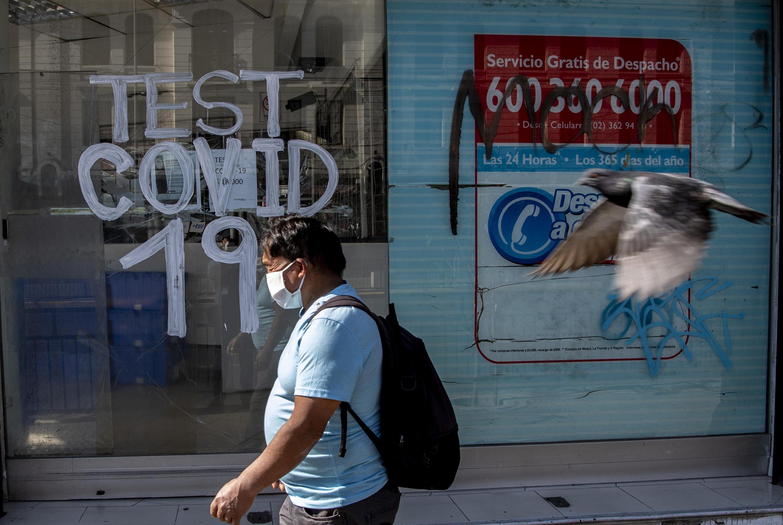 Una persona pasa junto a una farmacia donde se realizan pruebas de Covid-19 en la comuna de Recoleta, puesta en cuarentena para frenar la propagación del nuevo coronavirus COVID-19, en Santiago, el 6 de mayo de 2020.