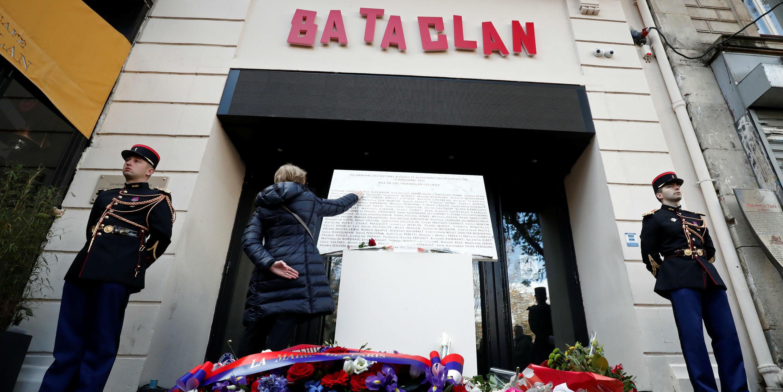 Una mujer toca la placa conmemorativa en la entrada de la sala de conciertos Bataclan, después de una ceremonia que recuerda el tercer aniversario de los ataques, en noviembre de 2015, en el que murieron 130 personas, en París, Francia, el 13 de noviembre de 2018.
