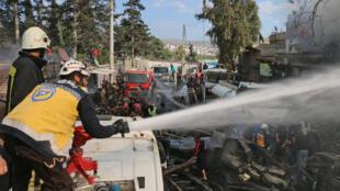 """صورة نشرها الدفاع المدني السوري """"الخوذ البيضاء"""" لاثنين من عناصره يعملان على إخماد حريق جراء انفجار صهريج للوقود في عفرين في 28 نيسان/أبريل 2020"""