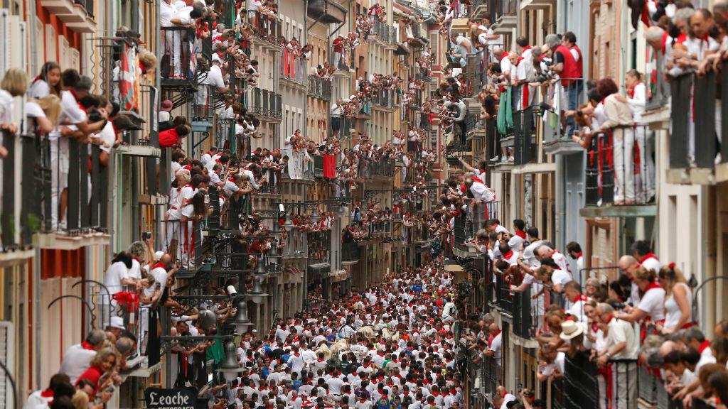 La gente mira desde los balcones mientras los corredores van frente a los toros y los novillos durante la primera corrida de toros en el festival de San Fermín en Pamplona, España, el 7 de julio de 2019.