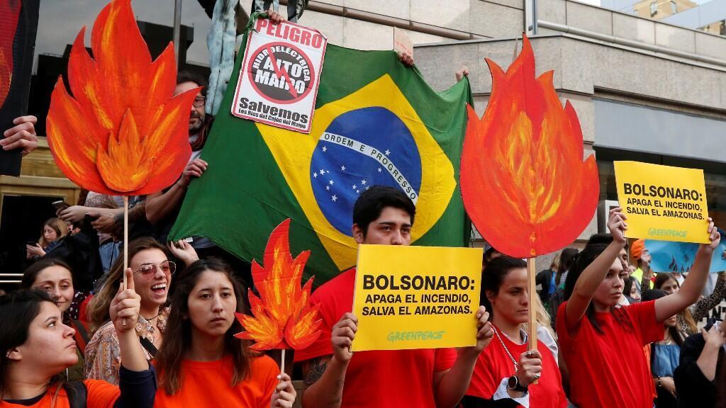 Manifestantes de organizaciones medioambientales participan en una manifestación frente a la embajada de Brasil para exigir más protección de la Amazonía en Santiago.