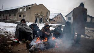 En Serbie, les migrants tentent de se réchauffer autour d'un feu.