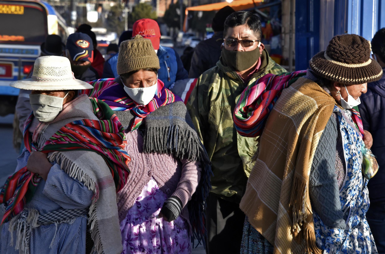 Personas que llevan máscaras faciales caminan por las calles de El Alto mientras Bolivia busca reactivar la economía en medio de la nueva pandemia del coronavirus.