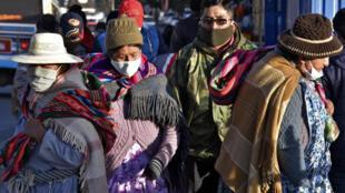 Las personas que llevan máscaras faciales caminan por las calles de El Alto mientras Bolivia busca reactivar la economía en medio de la nueva pandemia de coronavirus, el 1 de junio de 2020