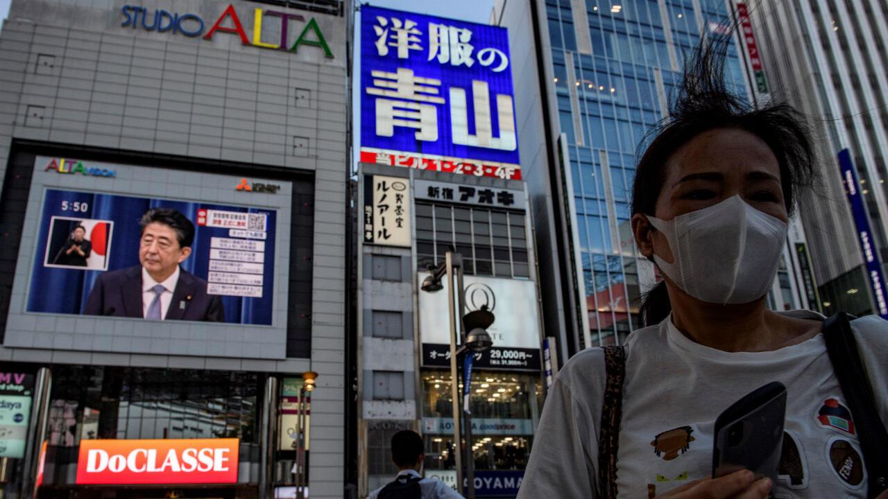 El primer ministro japonés, Shinzo Abe, se ve en una pantalla grande durante una conferencia de prensa en vivo en Tokio, el 28 de agosto de 2020.