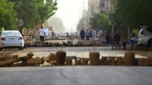 محتجون يغلقون شارعاً رئيسياً في الخرطوم لمنع الآليات العسكرية من المرور في المنطقة في 4 حزيران/يونيو 2019
