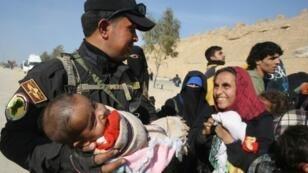 عنصر من وحدة مكافحة الإرهاب العراقية يحمل طفلا بين نازحين فروا من غربي الموصل خلال المعارك ضد الجهاديين، الخميس 9 آذار/مارس 2017