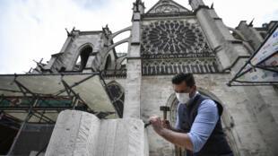 Un tailleur de pierre travaille sur le parvis de la Basilique de Saint-Denis, à Saint-Denis, en Seine-Saint-Denis le 5 juin 2020