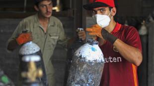 عاملان يملآن عبوتي اكسيجين، في مصنع في التاجي شمال بغداد في 5 تموز/يوليو 2020