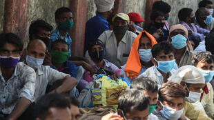Unos trabajadores migrantes esperan fuera de la estación de tren Chhatrapati Shivaji Maharaj de Bombay para regresar a sus localidades de origen en plena pandemia del coronavirus el 14 de mayo de 2020