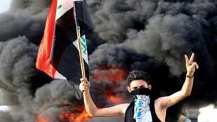 متظاهر يحمل علما في مظاهرات شهدتها العراق في 02أكتوبر 2019