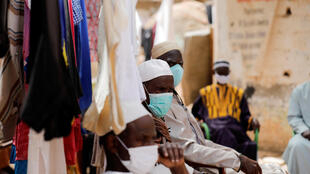 Men await the distribution of sanitary products by an aid group in the Liberte 6 Baraka district of Dakar, Senegal, on May 2, 2020. The countryhas recorded 1,886 coronavirus cases in total, including 19 deaths.