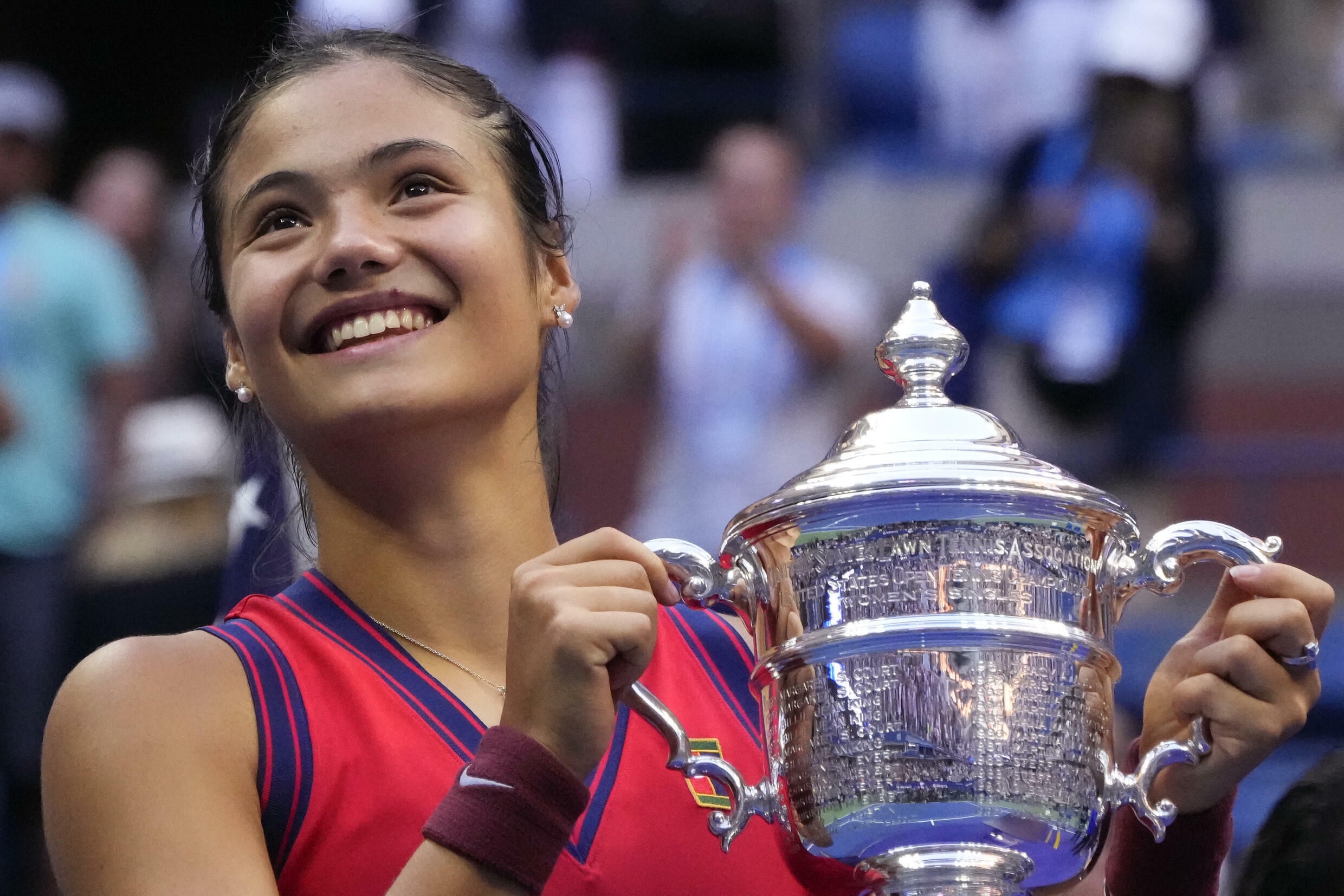 Winning smile: Britain's Emma Raducanu celebrates with the US Open trophy after becoming the first qualifier in history to win a Grand Slam