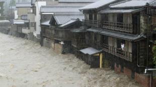 Des hommes observent le fleuve Isuzu qui a débordé après les fortes pluies causées par le typhon Hagibis à Ise, au Japon, le 12 octobre 2019.