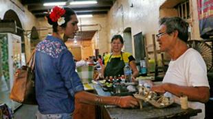 """La """"muxe"""" Estrella Vásquez habla con un zapatero en la comunidad de Juchitán en el estado de Oaxaca, México, el 26 de julio de 2017."""