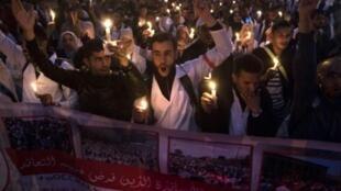 مدرسون شبان في المغرب رافعين شموعا مطالبين بعقود توظيف دائمة في وزارة التربية وذلك في العاصمة الرباط في 24 آذار/مارس 2019