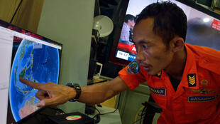 An official from Indonesia's national search and rescue agency points to the position where contact with the missing aircraft was lost