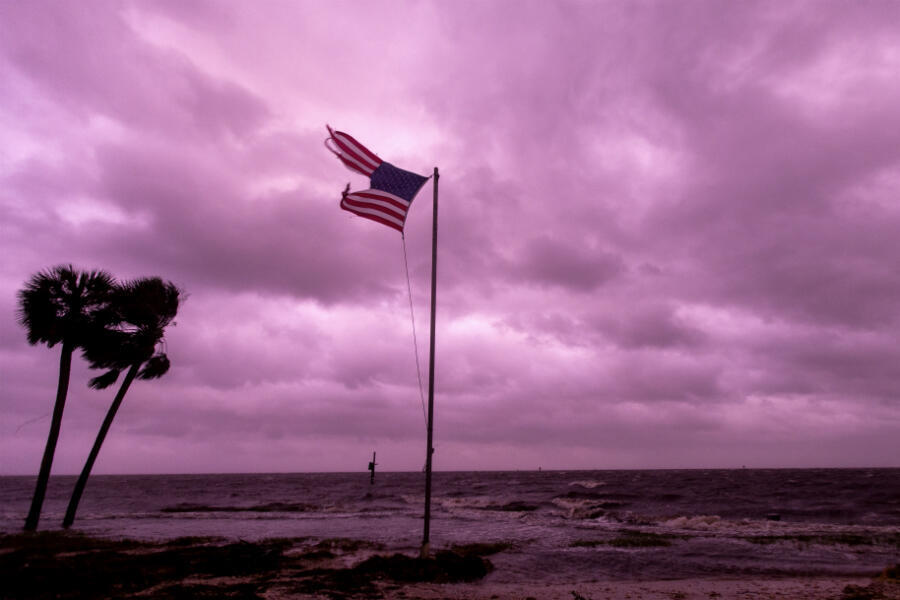 An American flag battered by Hurricane Michael continues to fly in the rose-colored light of sunset at Shell Point Beach on October 10, 2018, in Crawfordville, Florida.