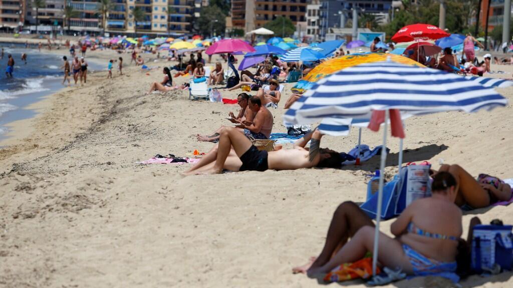 Varios bañistas disfrutan del primer día de libertad de movimientos en la playa de Palma de Mallorca. El 21 de junio de 2020.
