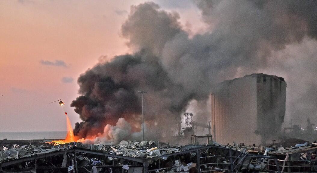 Un helicóptero apaga un incendio en el lugar de una explosión en el puerto de Beirut, la capital del Líbano, el 4 de agosto de 2020.