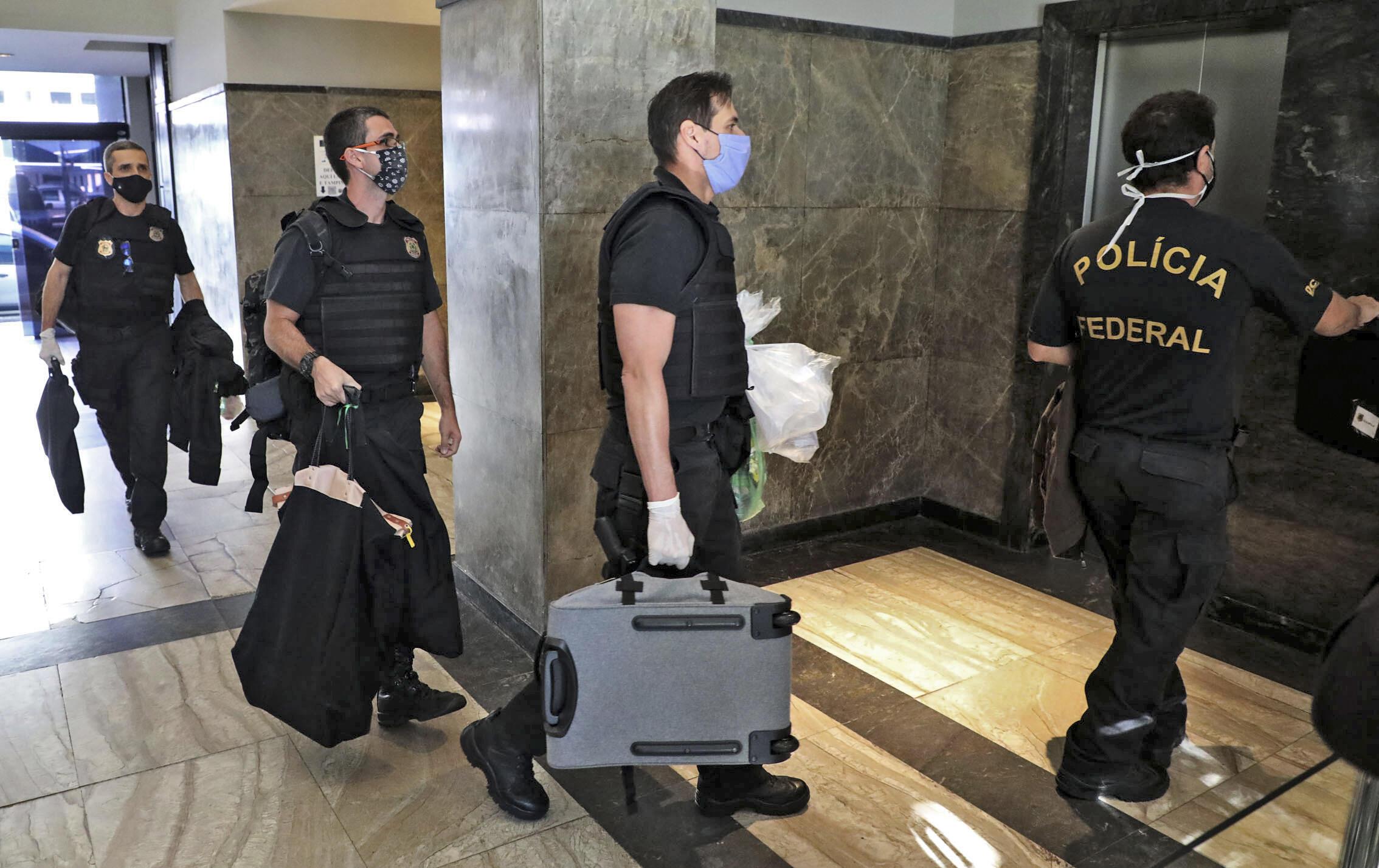 Agentes de la Policía Federal de Brasil cargan elementos incautados al gobernador de Rio de Janeiro, Wilson Witzel, tras allanar su residencia, el 26 de mayo de 2020