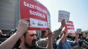 """Des manifestants brandissent des pancartes affichant """"Liberté pour les journalistes"""" lors d'un rassemblement pour la liberté de la presse le 3 mai 2017, à Istanbul."""