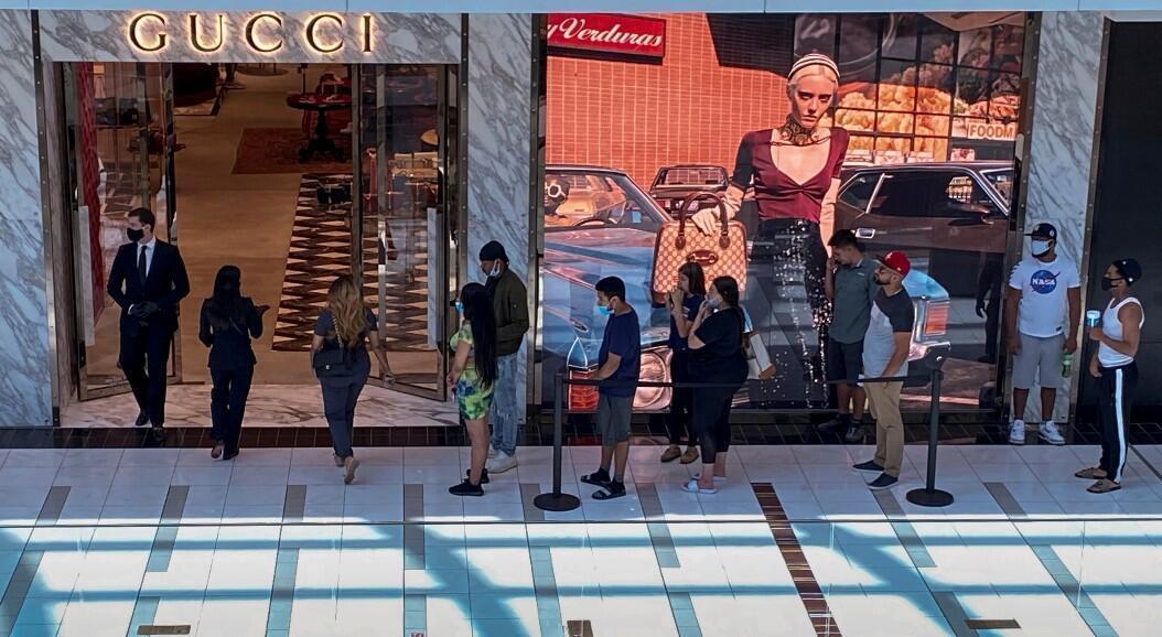 Archivo-Un grupo de personas hace fila para ingresar a una tienda de ropa, en Houston, Texas, el 1 de mayo de 2020.