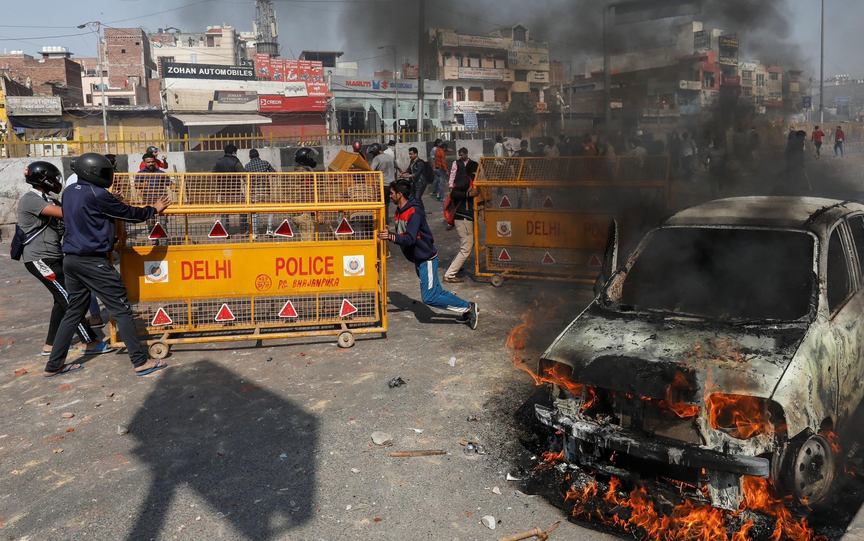 Simpatizantes de la ley de ciudadanía empujan las barricadas policiales durante un enfrentamiento con los opositores a la ley en Nueva Delhi, 24 de febrero de 2020