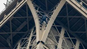Un homme grimpe la tour Eiffel le 20 mai 2019 à Paris