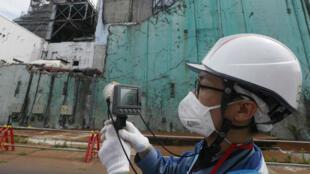 Un employé de la Tokyo Electric Power Company (Tepco) mesure en juillet 2018, les niveaux de radioactivité des réacteurs 2 et 3 de la centrale nucléaire de Fukushima.