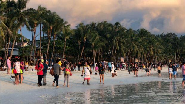 Los turistas se divierten durante la puesta de sol en Boracay, Filipinas, 26 de octubre de 2018.