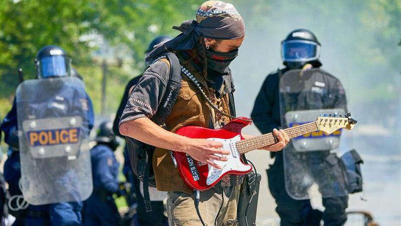 Un manifestante toca la guitarra durante una protesta en el marco del G7 en Quebec, Canadá, el 8 de junio de 2018.