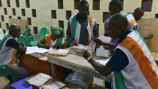 Trabajadores realizan el conteo de las papeletas electorales durante las elecciones regionales y municipales de Costa de Marfil en un centro de votación de Bouaké. 13 de octubre de 2018.