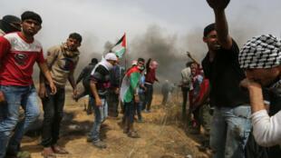 Manifestantes palestinos retiran parte del alambre de púas israelí durante enfrentamientos con las tropas israelíes, el 20 de abril de 2018.