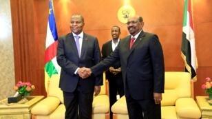 El presidente de la República Centroafricana, Faustin-Archange Touadera, le da la mano al presidente de Sudán, Omar al-Bashir, antes de firmar un acuerdo de paz entre el Gobierno de la República Centroafricana y 14 grupos armados luego, de dos semanas de conversaciones en la capital sudanesa, Jartum, el 5 de febrero de 2019.