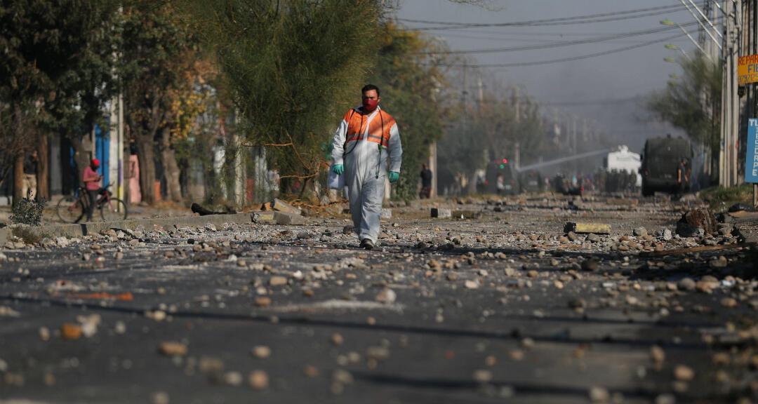 Un hombre vestido con un traje protector camina por una calle llena de piedras con las que manifestantes se enfrentaron a la Policía en medio de protestas contra la falta de ayudas para sobrellevar la cuarentena por coronavirus. Santiago, Chile, el 18 de mayo de 2020.