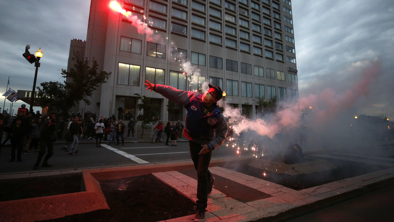 Un manifestante lanza una bengala en una marcha de protesta durante la Cumbre del G7 en la ciudad de Quebec, Canadá.