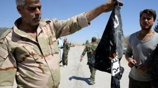 جندي سوري يحرق علم التنظيم في القريتين قرب حمص 4 أبريل/نيسان 2016